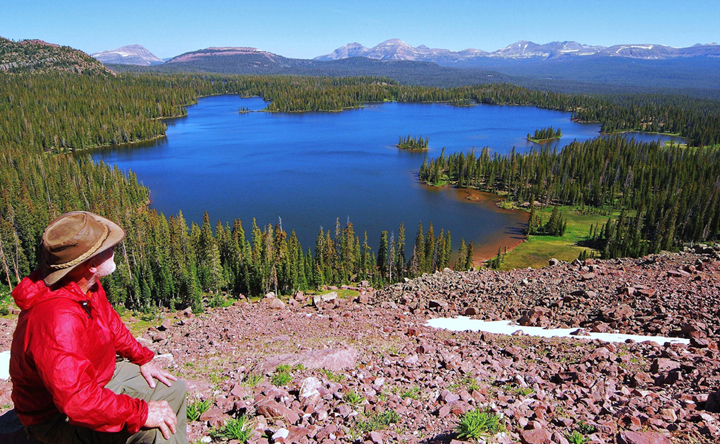 A single hiker looks down onto a dark blue lake surround by thick forest with a mountain range rising up over the horizon.
